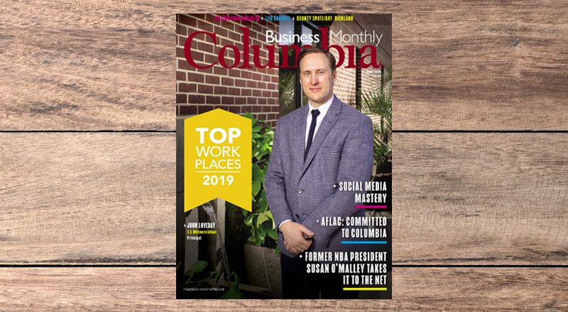Columbia Business Monthly magazine cover on wood background